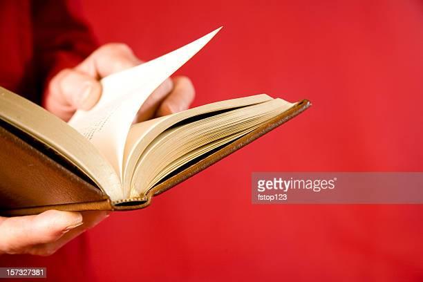 Livre ouvert de l'homme mains sur fond rouge