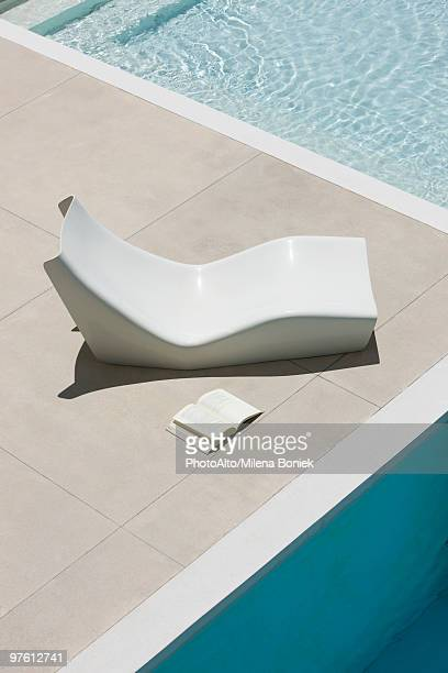 Open book lying on ground next to poolside deckchair