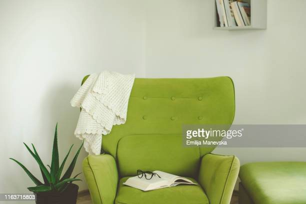 open book on a green armchair - armchair stock pictures, royalty-free photos & images