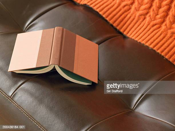 Open book on leather chair, elevated view