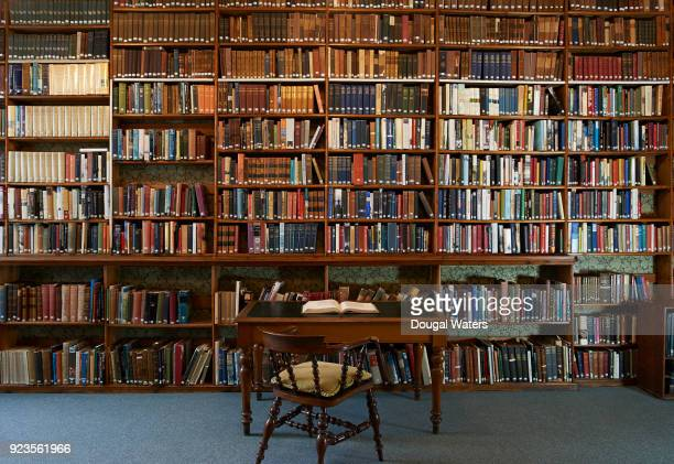 Open book on writing desk in traditional library.