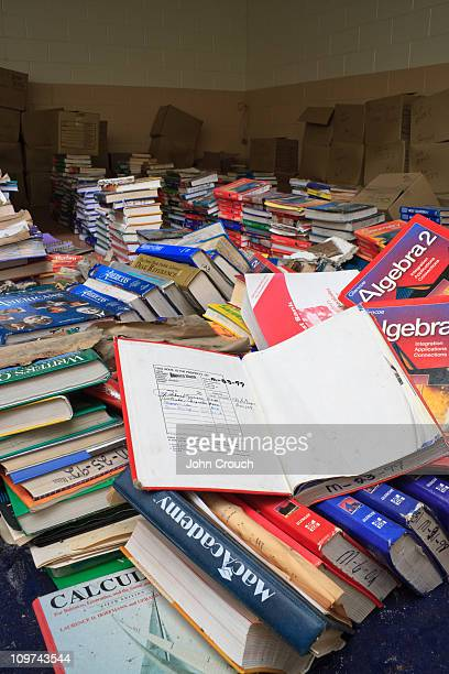 Open book sitting atop a large pile of textbooks