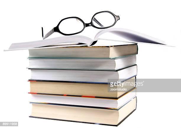 Pila de libro abierto y gafas