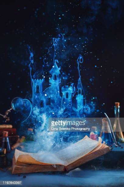 open book with a fantasy castle made of magical smoke. reading and imagination concept - paranormal stock pictures, royalty-free photos & images