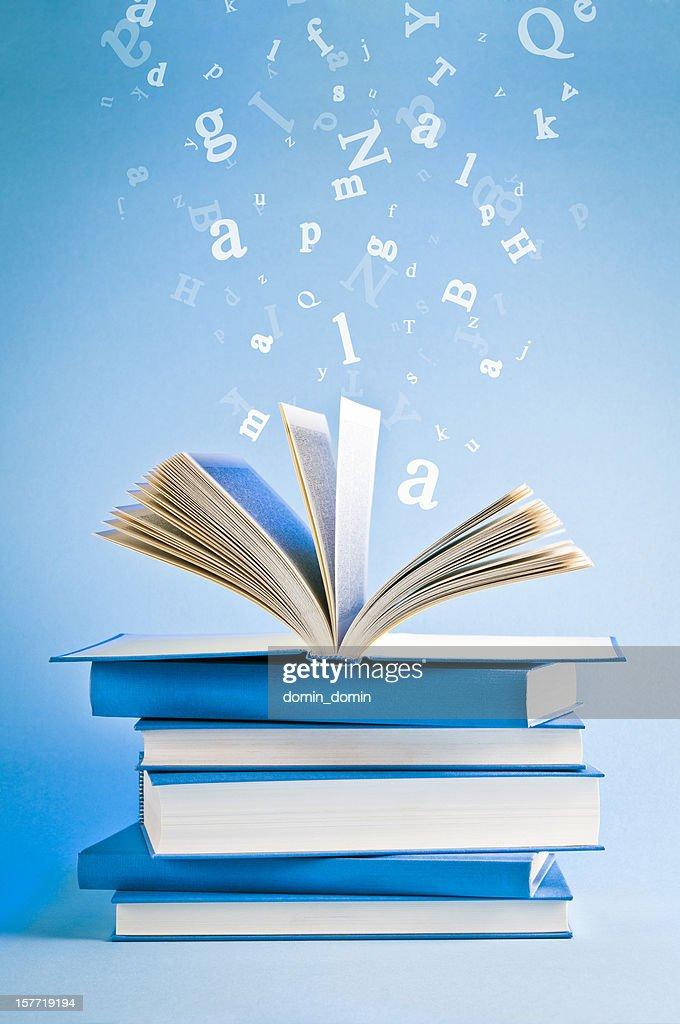 Livro aberto com letras espalhadas voando, isolado em Fundo azul : Foto de stock