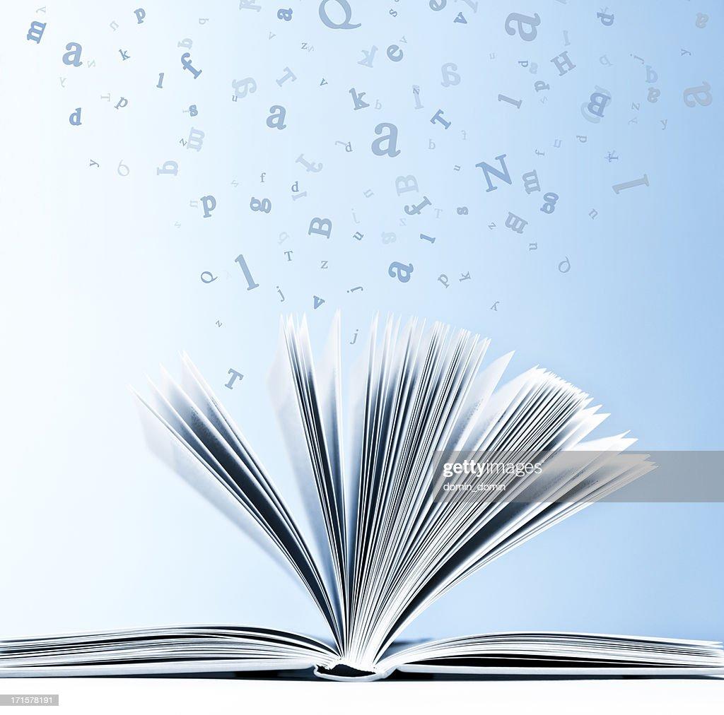 Offene Buch mit fliegenden, verstreuten Buchstaben isoliert auf Blau Hintergrund : Stock-Foto