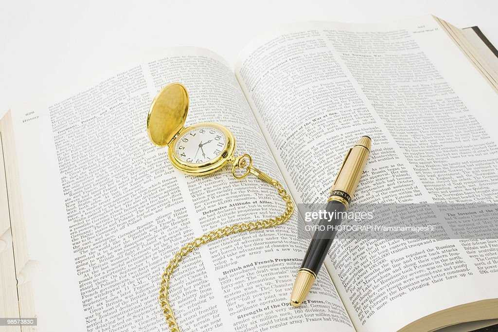 Open book with fountain pen and pocket watch : Stock Photo