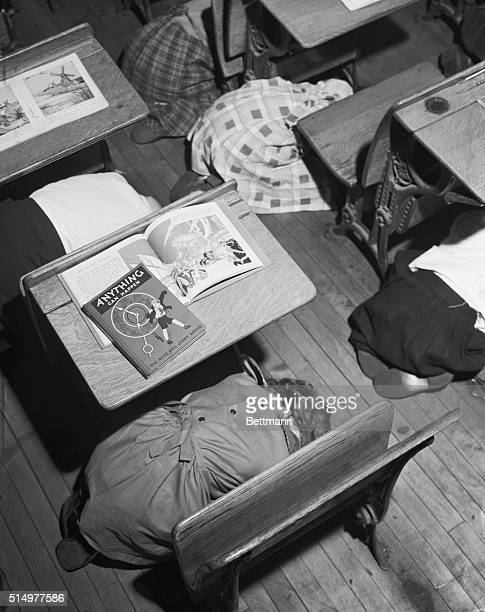 Open books are left on desks of the children of class 42Junior High Elementary as they dive under their desks during an 'A' bomb drill Top view of...