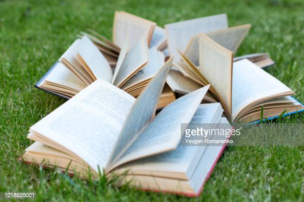 open books lying on a green grass. the concept of learning outdoors - literature ストックフォトと画像