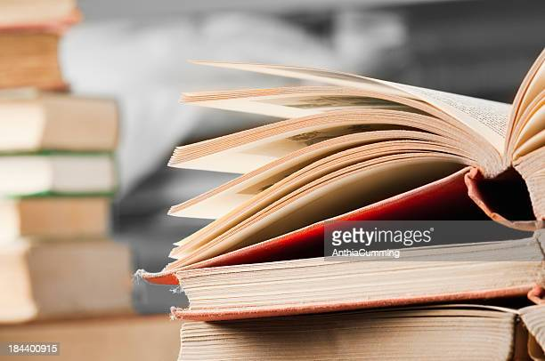 Open books on desk with stack of books in background
