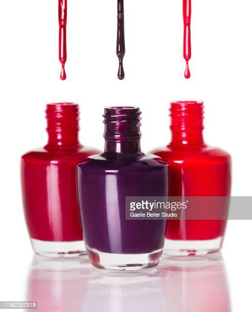 Open Bottles of Colored Nail Polish and Dripping Brushes