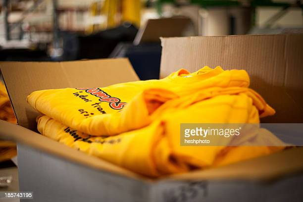 Open cardboard box containing screen printed t-shirts