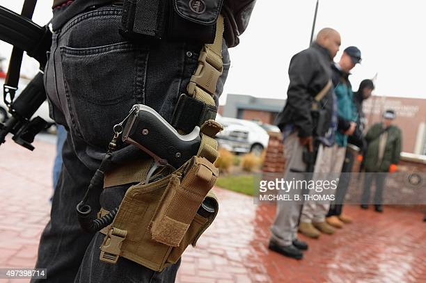 Open carry gun activists participate in a march in front of the city police department and minicipal court on November 16 2015 in Ferguson Missouri...
