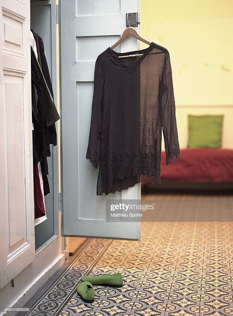Open closet with blouse hanging from door. : Stock Photo