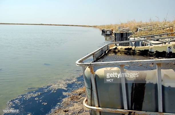 Open containers of crude waste sits near a lake of produced water near an oil production facility in Southern Sudan's Melut County. A Chinese...