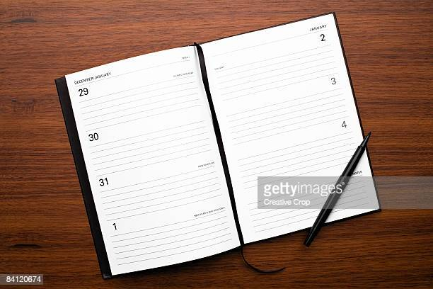 Open diary New Years Day on wood background