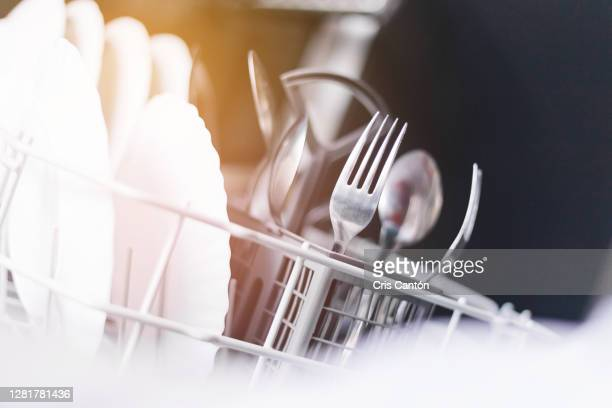 open dishwasher with clean dishes and cutlery - cris cantón photography fotografías e imágenes de stock