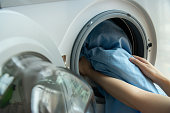 Open door in washing machine with blue bed sheets inside close up