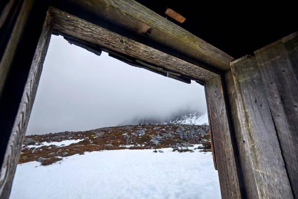 Open door of wooden cabin, hut in snow, emergency shelter for hikers, Australia
