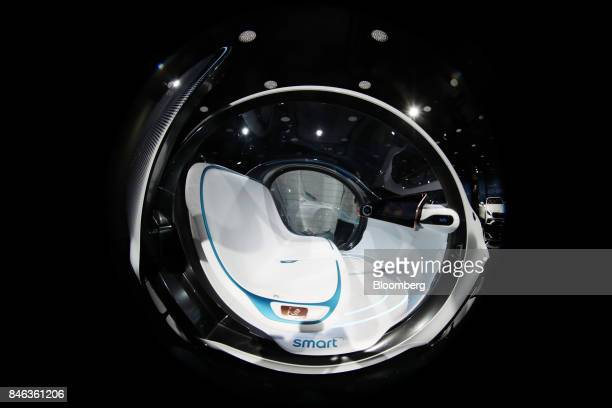 Open doors reveal the seat and interior of a Daimler Smart Vision EQ fortwo electric autonomous selfdriving concept automobile during the first media...