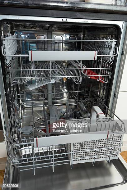 Open, empty and clean dishwasher in kitchen