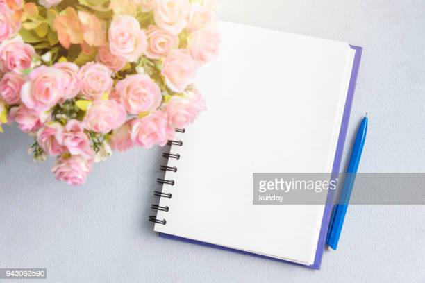 Open empty page of notebook with flower and pen on table.