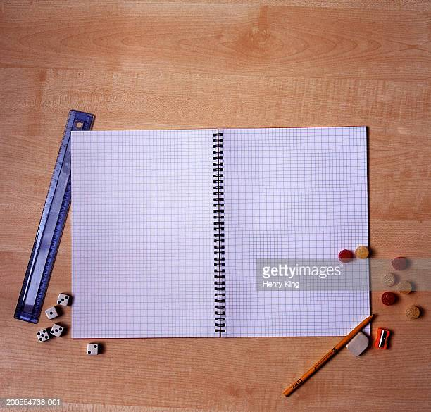 Open exercise book, with ruler, sweets and dice on wooden desk, overhead view