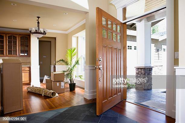 Open front door, rolled up rug and cartons on floor