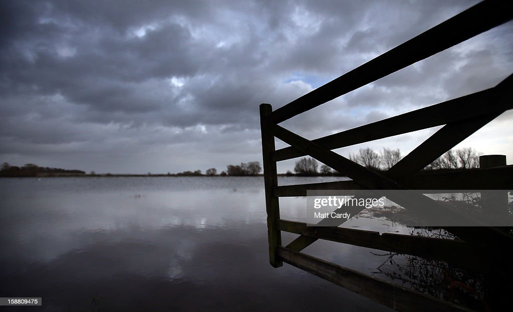 A open gate leads into fields covered in flood waters surrounding the village of Muchelney, which has been cut off by flooding on the Somerset Levels, on December 30, 2012 near Langport, England. The Met Office is warning of the risk of further flooding towards the end of the year, meaning 2012 is set to be the wettest on record.