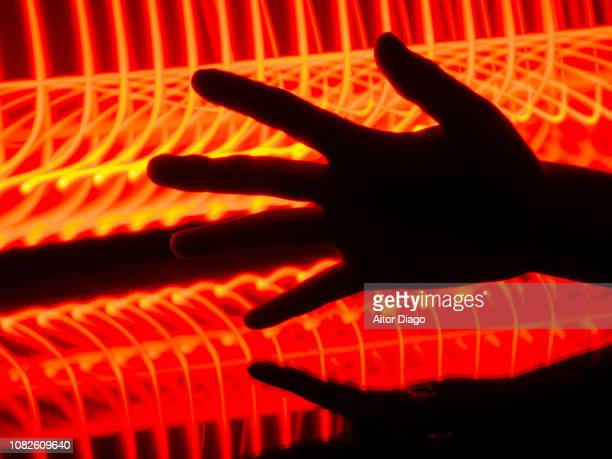 open hand reflected on reflective surface. the red and yellow lines of the background give a sensation of heat, fire. light painting. conceptual nature - wärme stock-fotos und bilder