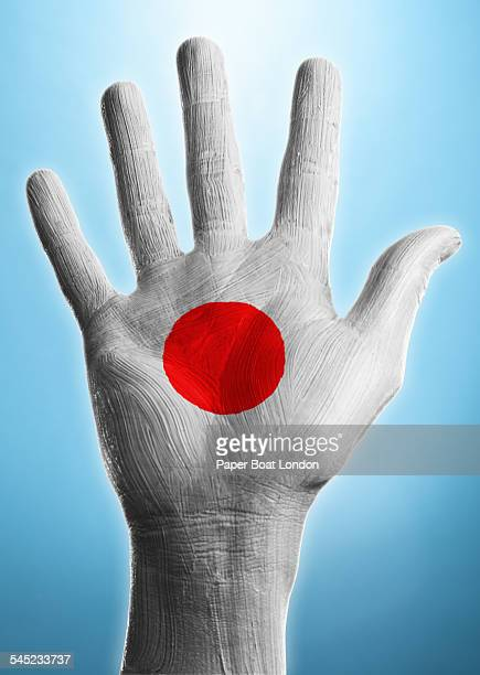 Open hand with flag of Japan painted on it