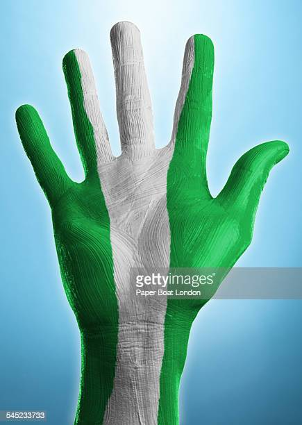 open hand with flag of nigeria painted on it - nigerian flag stock photos and pictures