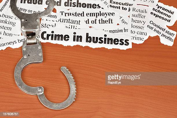 Open handcuffs next to headlines about business crime on desk