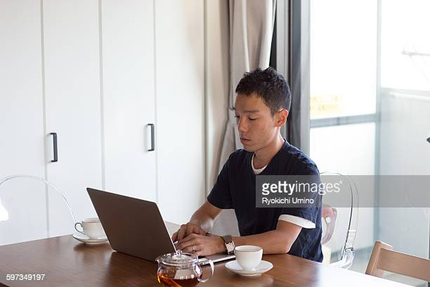 Open his laptop to work at home