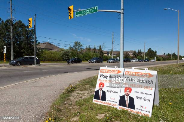 Open house signs are displayed on the side of a road in Brampton Ontario Canada on Saturday May 20 2017 After a double whammy of government...