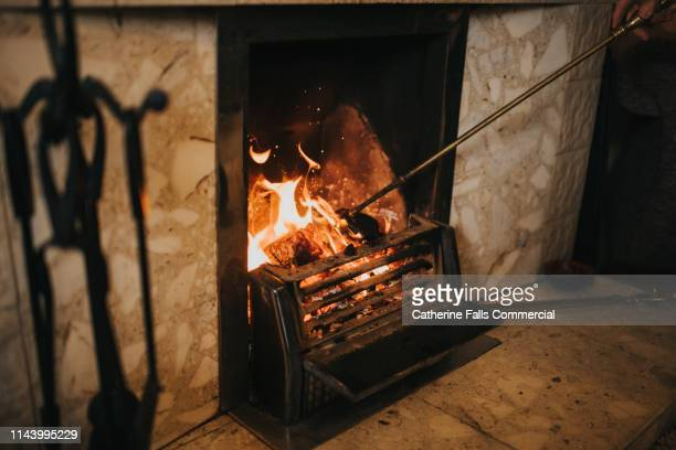 open log fire - stoking stock pictures, royalty-free photos & images