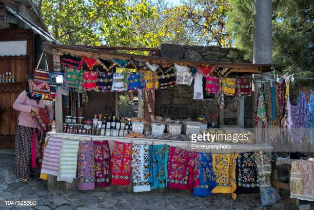 open market stand with a saleswoman in traditional clothing selling local food and textile products at behramkale town,northern aegean turkey.. - emreturanphoto bildbanksfoton och bilder