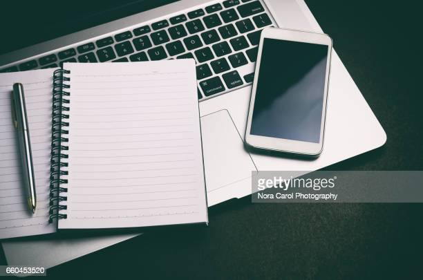Open note pad on top of laptop with smart phone