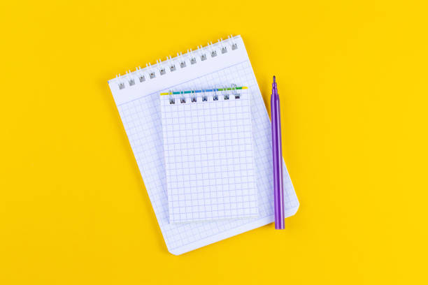 Open notebook on bright yellow paper background with pen