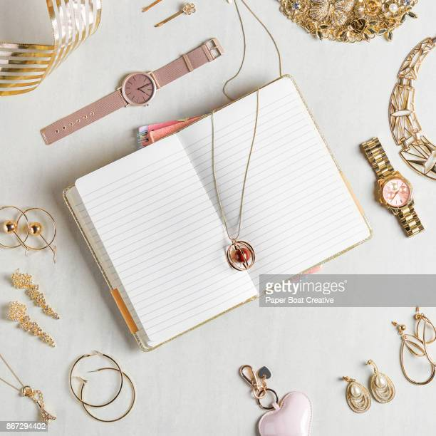 Open notebook with blank pages styled with different accessories like watches and necklace and other jewelries