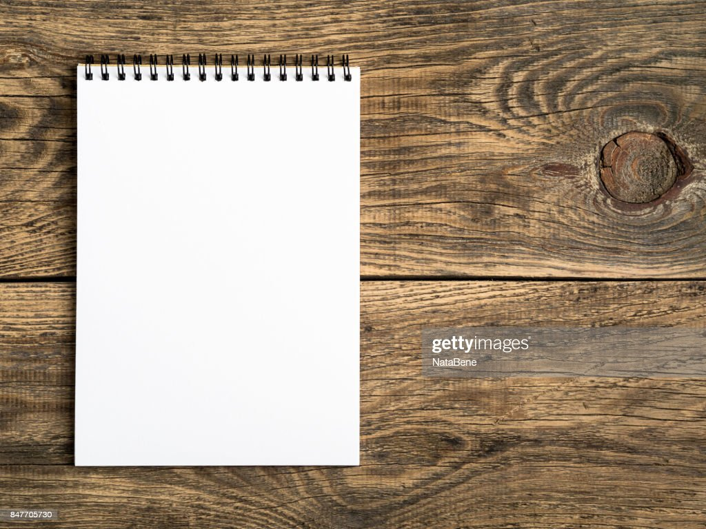 Open Notepad With A Clean White Page On Wooden Table Top View Stock Photo