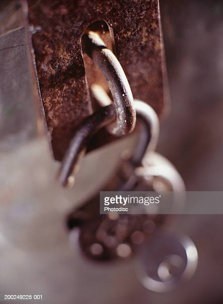 Open padlock hanging from latch