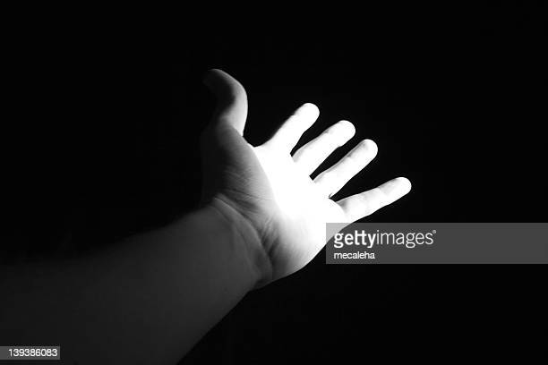 Open palm hand reaching out into darkness