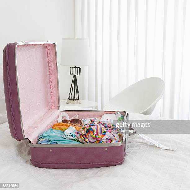 Open pink suitcase on bed