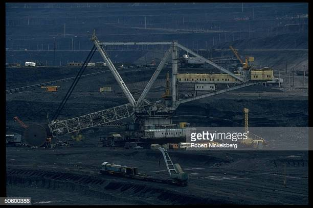 Open pit coal mine extracting machinery in motion w freight car on tracks at 1 of world's largest such ops in Central Steppes region Ekibastuz
