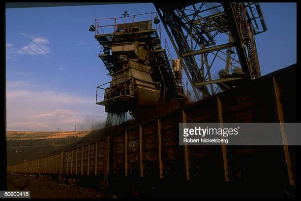 Open pit coal mine machine in in motion loading freight cars w freshly extracted ore at 1 of world's largest coal mine ops in Central Steppes region...