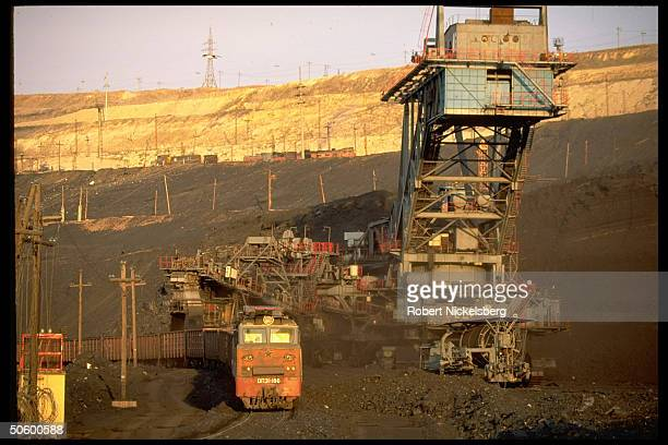 Open pit coal mine machinery framing waiting freight cars used to transport ore at 1 of world's largest coal mine ops in Central Steppes region...