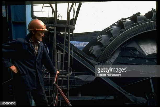 Open pit coal mine worker framed by Russianmade bucket wheel excavator operating at 1 of world's largest coal mine ops in Central Steppes region...