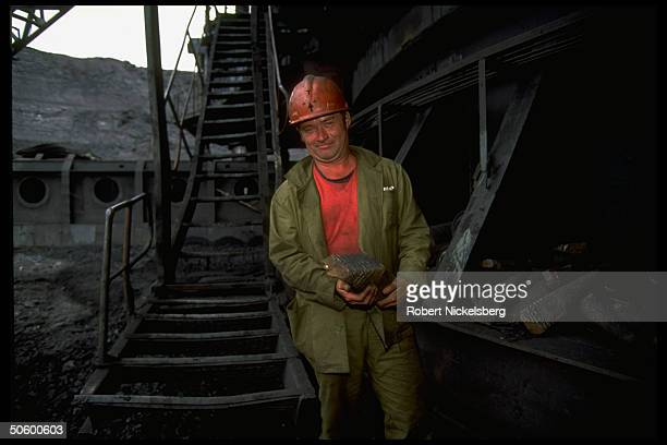 Open pit coal mine worker holding ore hunk at 1 of world's largest coal mine ops in Central Steppes region Ekibastuz