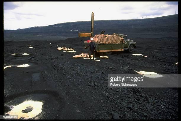 Open pit coal mine workers spreading sacks of granular substance fr truckload on marked circles in Central Steppes region Ekibastuz